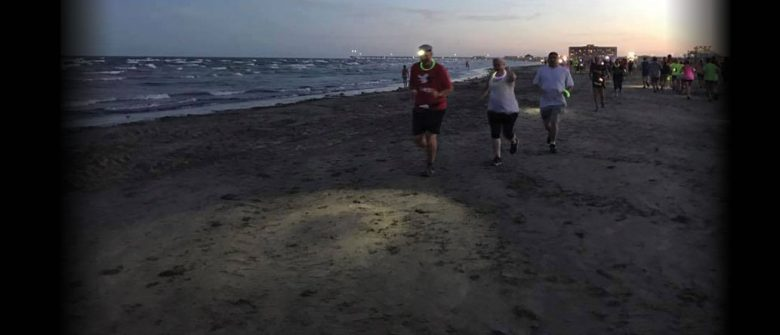 Lloyd running on the beach in Port Aransas at the Sand Crab Beach Run, wearing his Coast HL7 headlamp