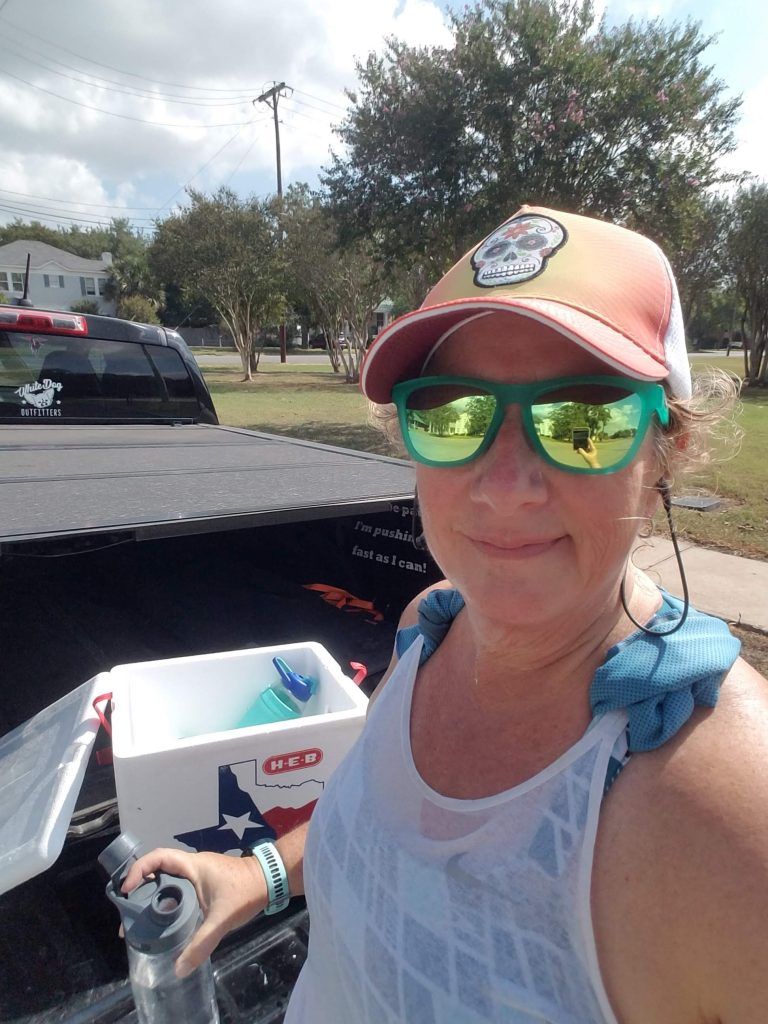 Ice chest in back of truck with water bottles, runner with hat and sunglasses